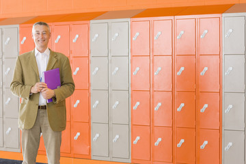 Smiling teacher standing near lockers in school corridor