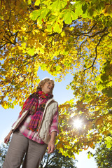 Smiling senior woman walking through park beneath autumn leaves