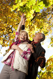 Smiling senior couple picking autumn leaves from tree together