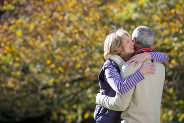 Romantic senior couple hugging in autumn park