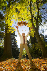 Laughing senior man throwing autumn leaves in air