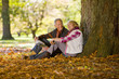 Happy senior couple reading book under tree covered in autumn leaves