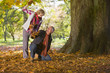 Playful senior couple throwing autumn leaves at one another