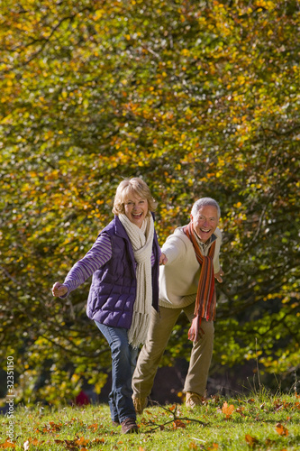 Happy senior couple holding hands and walking outdoors in autumn