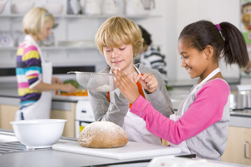 Smiling students flouring bread in home economics class