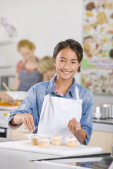 Smiling student putting sprinkles on cupcakes in home economics class