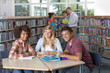 Students studying together in study group in school library