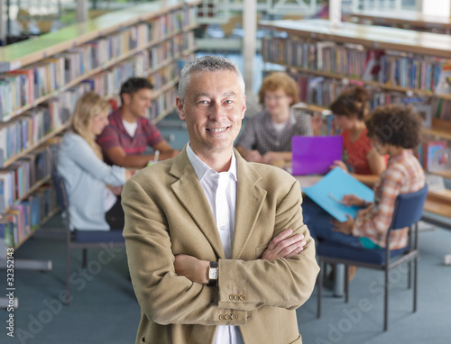 Smiling teacher standing in school library with study group on background