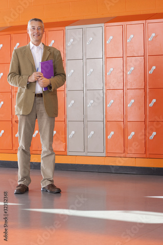 Smiling teacher standing near lockers in school hallway