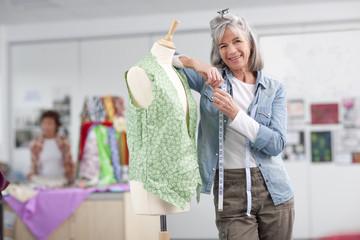 Smiling designer adjusting shirt on dressmaker's dummy in classroom