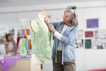 Designer adjusting shirt on dressmaker's dummy in classroom