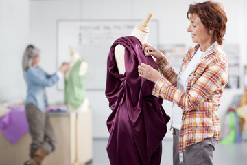 Smiling designer adjusting evening gown on dressmaker's dummy in classroom