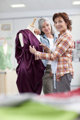 Designers assessing evening gown on dressmaker's dummy in classroom