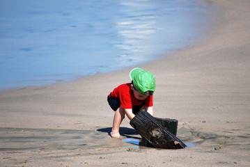 boy looking for treasure under log
