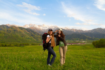 two girls with a backpack in the mountains