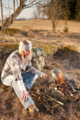 Hiking woman with backpack cook by campfire