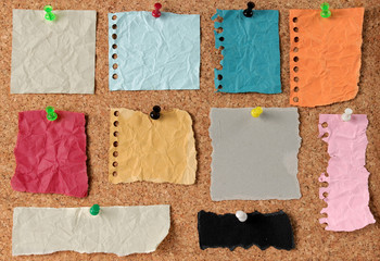 set of note paper pinned to a cork board