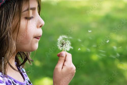 fillette soufflant un pissenlit