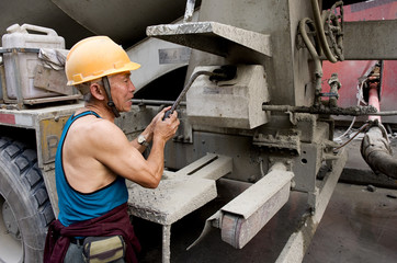 laborer and truck-concrete mixer on construction site