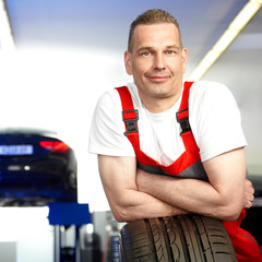 Motor mechanic with a summer tyre in a garage