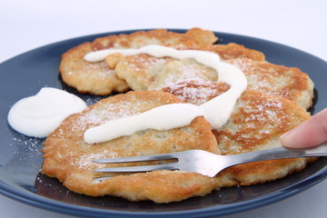 Potato pan cakes with cream and sugar being eaten with a fork
