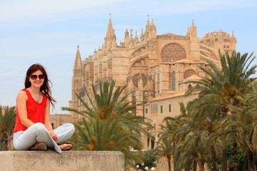 Young woman sitting in front of La Seu Cathedral in Majorca