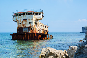 Rusty sunken ship among the sea rocks