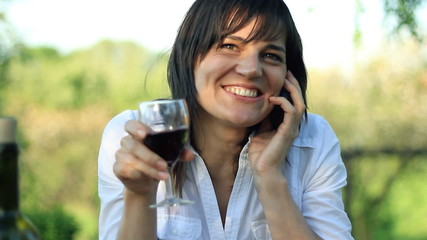 Beautiful happy woman drinking wine and taking on cellphone