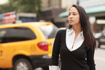 Image of a woman with a taxi cab in the background