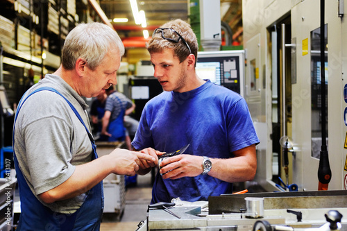 skilled workers controlling a workpiece - 32413107
