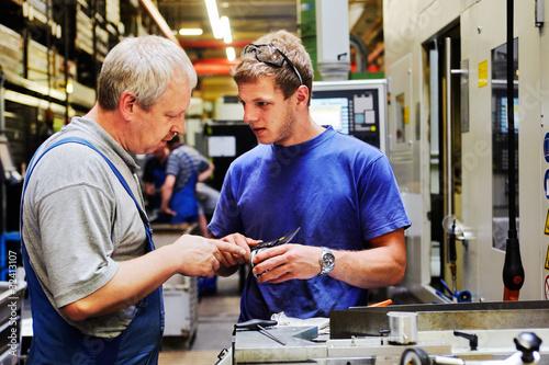 Leinwanddruck Bild skilled workers controlling a workpiece