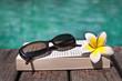 Livre et lunettes de soleil à la piscine