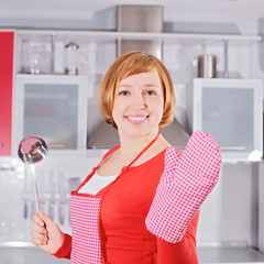 Beautiful young housewife in kitchen holding ladle