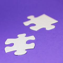 Puzzleteile vor Lila Hintergund
