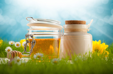 Healthy food - jars of honey and spring flowers