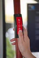 Mano de mujer pulsando parada de autobús