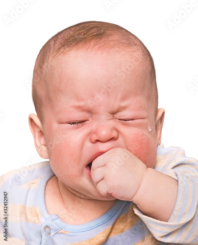 The crying boy in tears, hand in mouth, on  white background