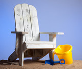 White adirondack chair with shovel and pail on sand and sky