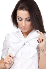 Portrait of young female tying a bow on white background