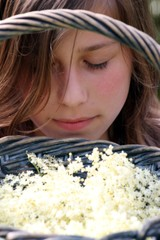 Mädchen hält Korb mit Hulunder und riecht daran