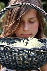 Mädchen riecht an Korb mit Holunder