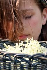 Mädchen riecht verträumt an Holunder