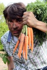 gärtner hält geerntete Mohrrüben ans Gesicht