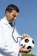 doctor with ball and stethoscope in blue sky