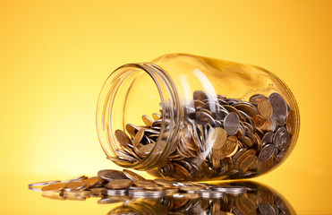 coins spilling from a money jar on yellow background. Ukrainian