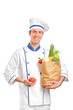Smiling chef holding a tomato and paper bag full with vegetables