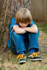 bambino seduto appoggiato ad un albero