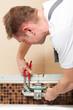 Installateur bringt Mischbatterie im Bad an