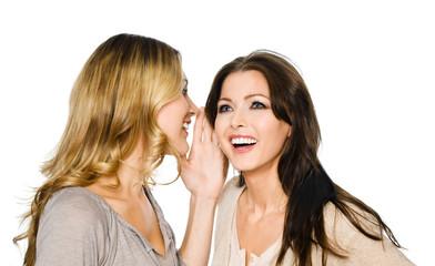Frau flüstert einer Frau in ihr Ohr
