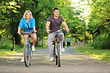 Happy couple biking in the park